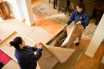 Two Hispanic women pack up painting at clients home