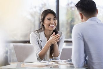 Smiling businesswoman meets with a male colleague.