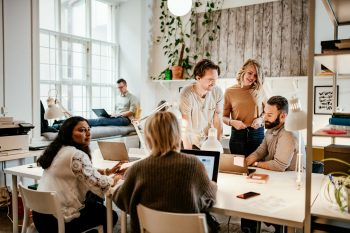 Diverse group of happy employees gathered around a table in a modern office