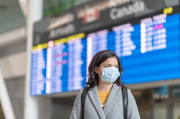 A solo travellers flight has been cancelled. She is standing in front of the departures board. She is wearing a protective face mask. Travelling during the COVID-19 pandemic.