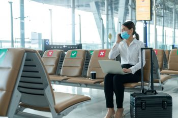 Woman sitting in airport talking on cell phone and using laptop