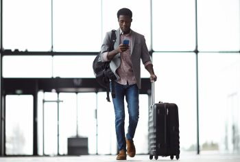 Young mobile traveler walking through the airport while looking at his phone